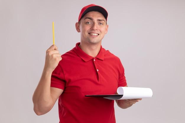 흰 벽에 고립 된 연필을 올리는 클립 보드를 들고 모자와 유니폼을 입고 감동 젊은 배달 남자