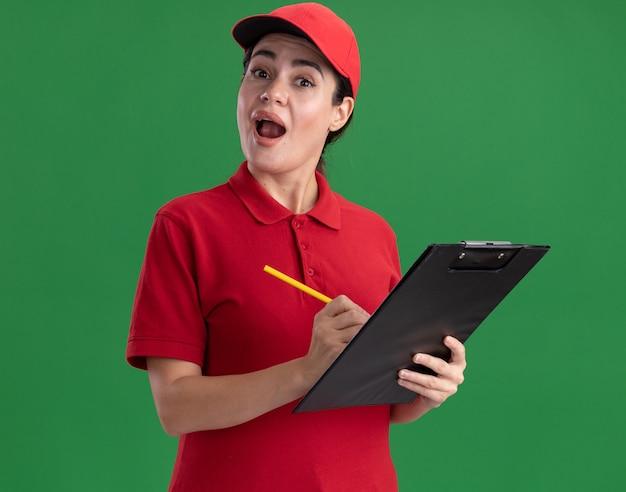유니폼을 입고 클립보드와 연필을 들고 벽에 격리된 전면을 바라보는 모자를 쓴 젊은 배달 여성