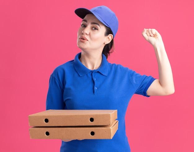 분홍색 벽에 격리된 노크 제스처를 하는 유니폼과 모자를 들고 피자 패키지를 들고 있는 젊은 배달 여성