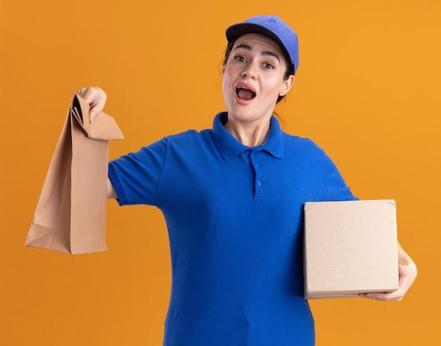 Impressionata giovane donna delle consegne in uniforme e cappuccio con scatola di cartone e pacchetto di carta isolato su parete arancione
