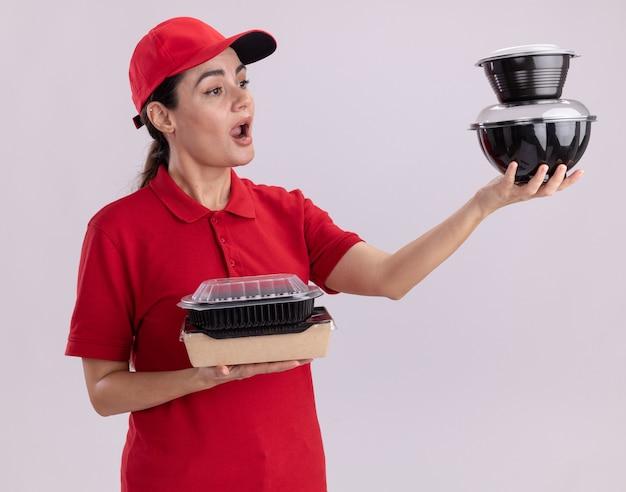 Impressionata giovane donna delle consegne in uniforme e cappuccio che tiene in mano un pacchetto di alimenti di carta e contenitori per alimenti che guardano i contenitori per alimenti