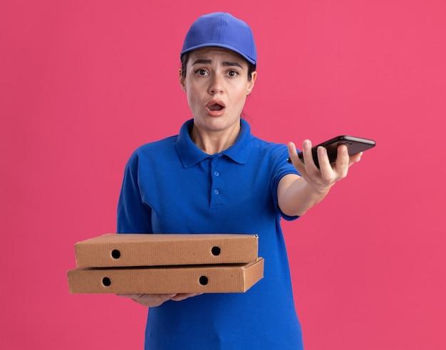 Impressionata giovane donna delle consegne in uniforme e berretto che tiene in mano i pacchetti di pizza che allungano il telefono cellulare verso la telecamera