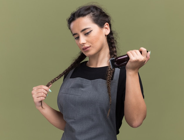 バリカンを持った制服を着た若い女性の理髪師は、オリーブグリーンの壁で隔離された髪をつかんだ