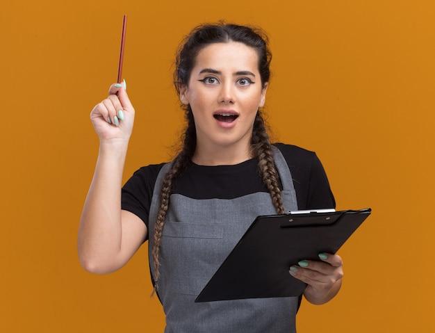 Impressionato giovane barbiere femminile in uniforme che tiene appunti e solleva matita isolato sulla parete arancione