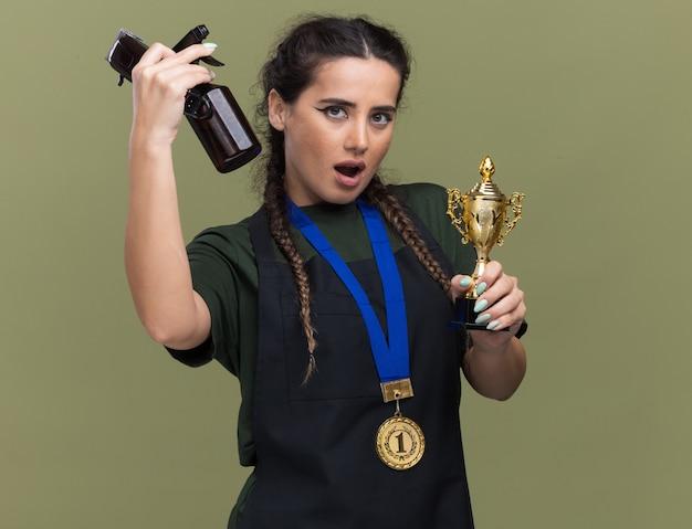 Giovane barbiere femminile colpito in uniforme e medaglia che tiene la tazza del vincitore e che alza gli strumenti del barbiere isolati sulla parete verde oliva