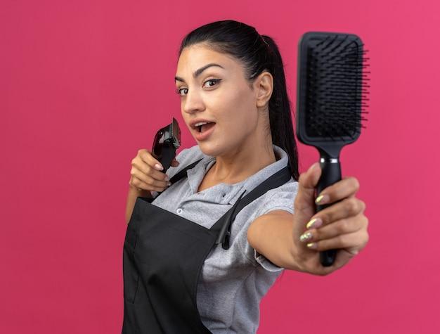 Впечатленная молодая женщина-парикмахер в униформе, стоящая в профиль, держа машинку для стрижки волос и протягивая гребень, изолированную на розовой стене