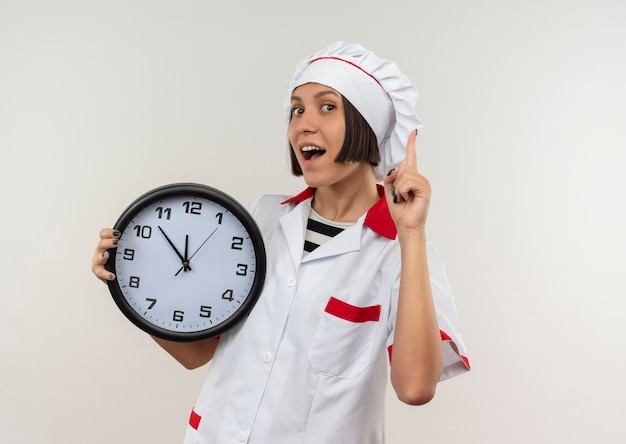 Impressionato giovane cuoco femminile in uniforme da chef tenendo l'orologio e alzando il dito isolato su bianco con lo spazio della copia