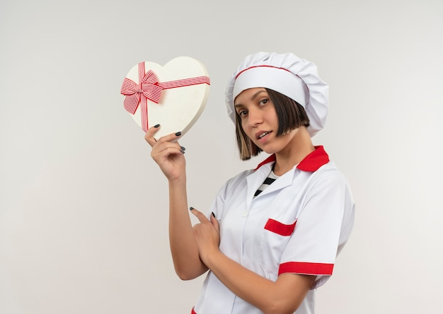 Impressionato giovane cuoco femminile in uniforme del cuoco unico che tiene il contenitore di regalo a forma di cuore isolato su bianco con lo spazio della copia