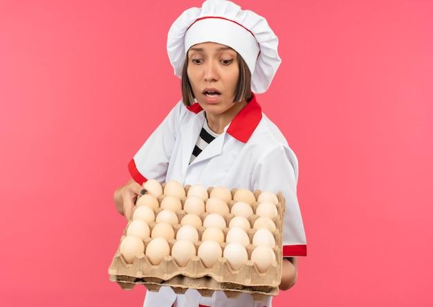 Impressionato giovane femmina cuoco in uniforme da chef tenendo e guardando il cartone di uova isolato su rosa con copia spazio