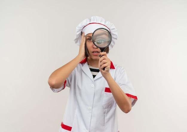 Impressionato giovane cuoco femminile in uniforme del cuoco unico che tiene e guardando attraverso la lente d'ingrandimento con la mano sulla testa isolata su bianco con lo spazio della copia
