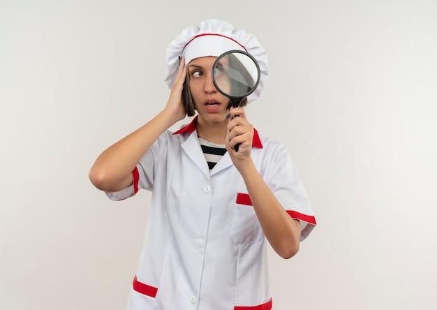 Impressionato giovane cuoco femminile in uniforme del cuoco unico che tiene la lente d'ingrandimento mettendo la mano sulla testa e guardando il lato isolato su bianco con lo spazio della copia