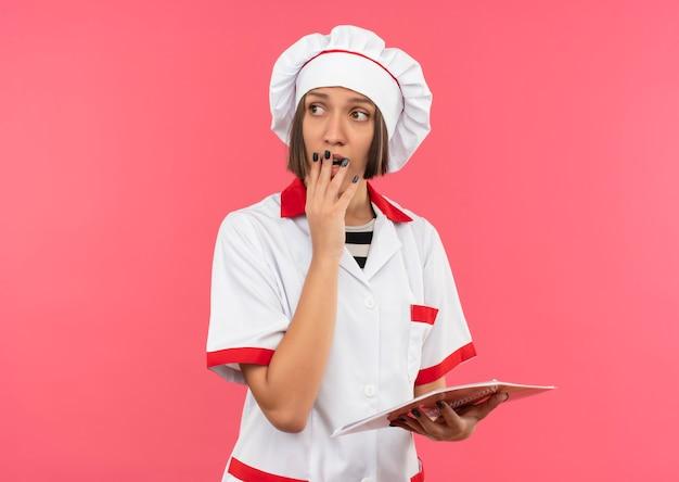 Impressionato giovane cuoco femminile nel blocco note della tenuta dell'uniforme del cuoco unico che mette la mano sulla bocca e che esamina il lato isolato sul colore rosa con lo spazio della copia