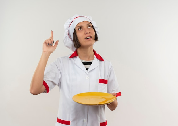 Impressionato giovane cuoco femminile in uniforme del cuoco unico che tiene piatto che osserva e che indica su isolato su bianco con lo spazio della copia