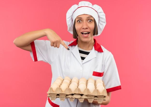 Impressionato giovane cuoco femminile in uniforme del cuoco unico che tiene e che indica al cartone delle uova isolato sul colore rosa