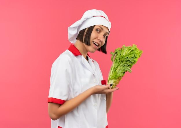 Impressionato giovane cuoco femminile in uniforme del cuoco unico che tiene e che indica con lattuga a mano isolata sul rosa