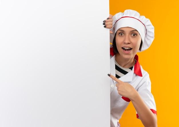 Impressionato giovane cuoco femminile in uniforme da chef guardando da dietro il muro bianco e indicandolo isolato sull'arancio con lo spazio della copia