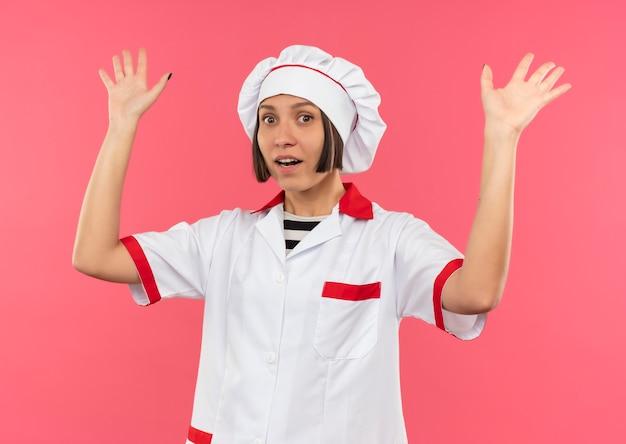Impressionato giovane femmina cuoco in uniforme da chef alzando le mani isolate sul rosa
