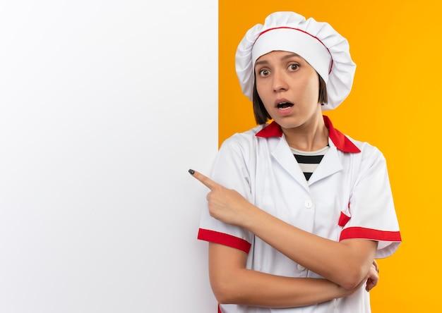 Impressionato giovane cuoco femminile in uniforme da chef in piedi davanti al muro bianco e indicandolo isolato sull'arancio con lo spazio della copia