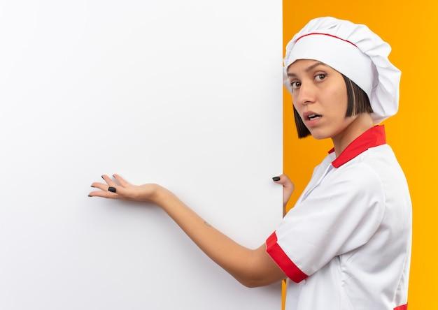 Giovane cuoco femminile impressionato in uniforme del cuoco unico che sta vicino alla tenuta bianca della parete e che indica con la mano isolata sull'arancio con lo spazio della copia