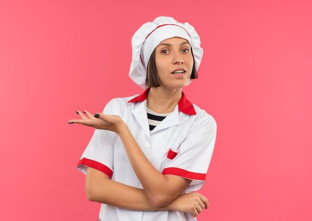 Giovane cuoco femminile impressionato in uniforme del cuoco unico che sta con la postura chiusa e che mostra la mano vuota isolata sul colore rosa con lo spazio della copia