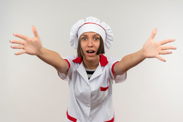 Giovane cuoco femminile colpito in uniforme del cuoco unico che allunga le mani isolate su bianco