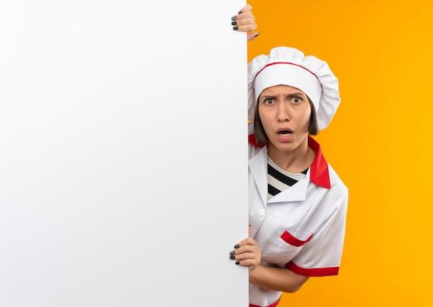 Impressionato giovane cuoco femminile in uniforme da chef giovane cuoco femminile in uniforme da chef tenendo e guardando da dietro il muro bianco isolato su con lo spazio della copia