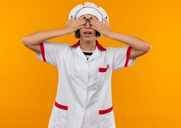 오렌지에 고립 된 손으로 눈을 감고 요리사 유니폼에 감동 된 젊은 여성 요리사