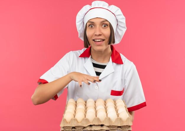Впечатленная молодая женщина-повар в униформе шеф-повара держит коробку с яйцами и держит руку над ними, изолированную на розовом