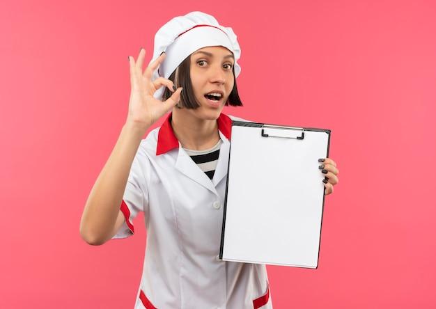 クリップボードを保持し、ピンクで分離されたokサインをしているシェフの制服を着た若い女性の料理人に感銘を受けました