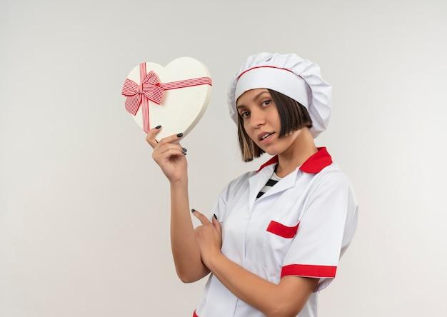 コピースペースで白で隔離のハート型のギフトボックスを保持しているシェフの制服を着た若い女性料理人に感銘を受けました