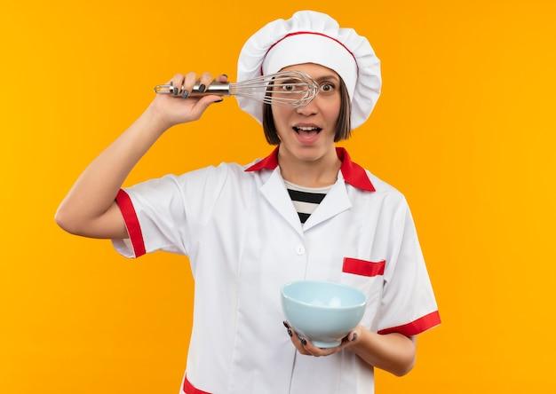 オレンジ色に分離された泡立て器を通して見ている泡立て器とボウルを保持しているシェフの制服を着た若い女性料理人に感銘を受けました