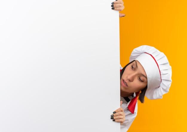 シェフの制服を着た若い女性料理人に感銘を受けました。コピースペースで隔離された壁の白い壁の後ろから見ているシェフの制服を着た若い女性料理人
