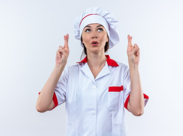 Impressed young female cook wearing chef uniform crossing fingers isolated on white wall