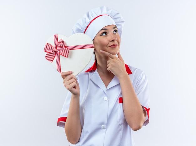 Impressionato giovane cuoca che indossa l'uniforme dello chef tenendo la scatola a forma di cuore afferrato il mento isolato sul muro bianco