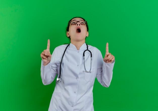 Впечатленная молодая женщина-врач в медицинском халате, стетоскопе и очках смотрит и указывает вверх изолированно на зеленой стене с копией пространства