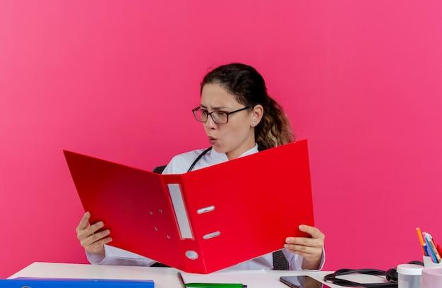 医療用ローブと聴診器と眼鏡を身に着けている感銘を受けた若い女性医師が机に座って医療ツールを保持し、分離されたフォルダーを見て