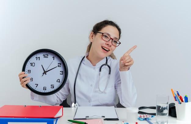 의료 가운 및 청진 기 및 의료 도구를 들고 시계를 들고 고립 된 측면을 가리키는 책상에 앉아 안경을 착용하는 감동 된 젊은 여성 의사