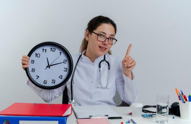 의료 가운과 청진 기 및 의료 도구를 책상에 앉아 안경을 착용하는 감동 된 젊은 여성 의사는 고립 된 손가락을 올리는 시계를 들고 찾고