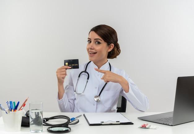 医療用ローブと聴診器を身に着けている感銘を受けた若い女性医師は、医療ツールとラップトップを持って机に座って、分離されたクレジットカードを指しています