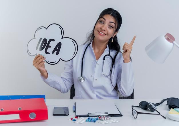 의료 가운과 청진기를 착용하고 의료 도구를 들고 아이디어 거품을 들고 책상에 앉아 감동하고 고립 된 손가락을 올리는 젊은 여성 의사