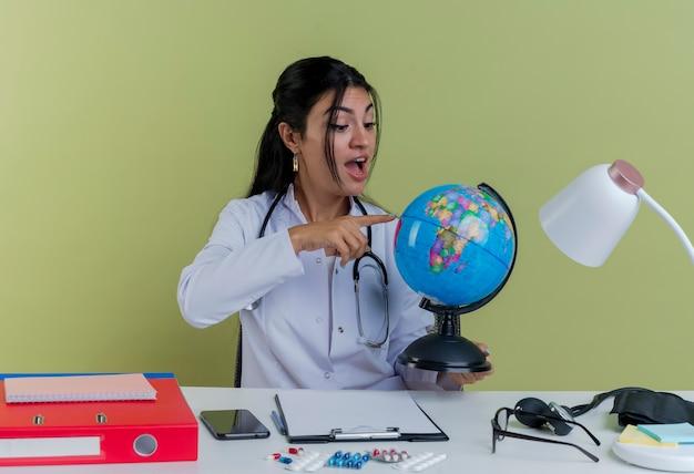 医療用ローブと聴診器を身に着けている感銘を受けた若い女性医師が机に座って医療ツールを保持し、地球を見て、指している