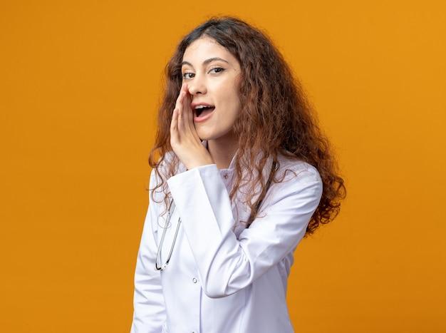医療用ローブと聴診器を身に着けている感銘を受けた若い女性医師がプロファイルビューに立って、コピースペースのあるオレンジ色の壁に隔離された口の近くでささやきながら手を保ちます Premium写真