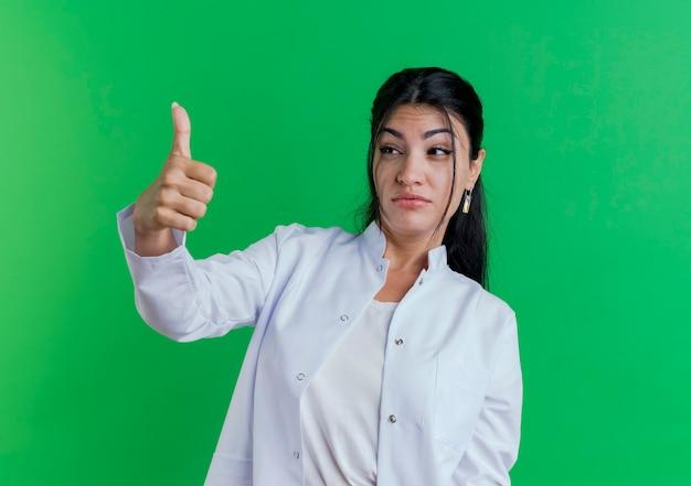 Впечатленная молодая женщина-врач в медицинском халате, глядя на сторону, показывающую большой палец вверх, изолированную на зеленой стене с копией пространства
