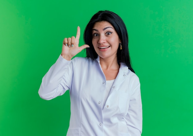 Impressed young female doctor wearing medical robe looking doing loser gesture