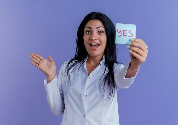 Impressionato giovane medico femminile che indossa un abito medico che mostra la nota di sì che mostra la mano vuota isolata sulla parete viola con lo spazio della copia