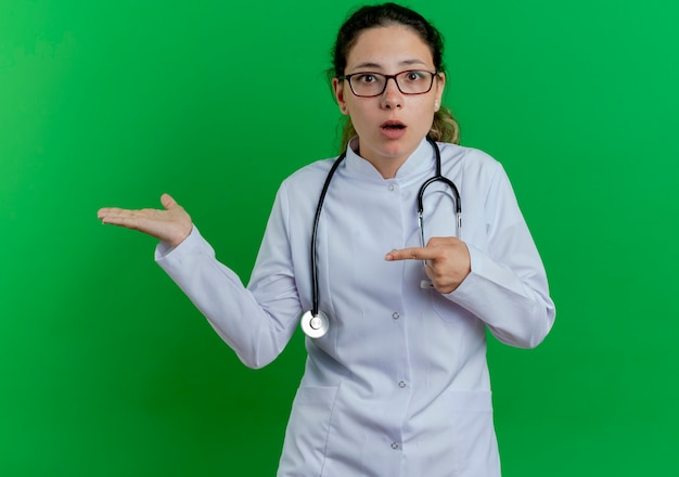 Impressionato giovane dottoressa che indossa veste medica e stetoscopio e bicchieri che mostrano la mano vuota e indicandola isolata sulla parete verde
