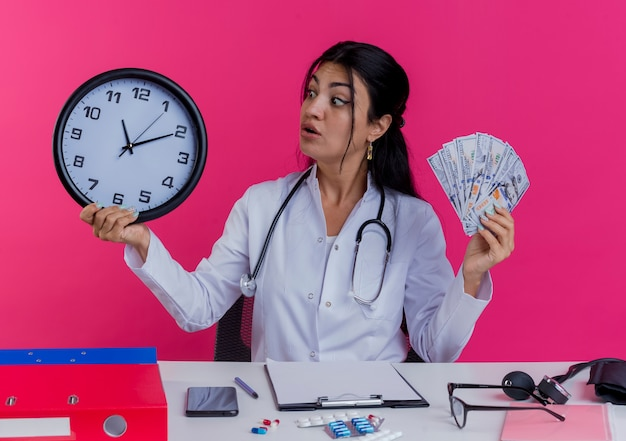 Impressionato giovane medico femminile che indossa abito medico e stetoscopio seduto alla scrivania con strumenti medici che tengono soldi e orologio guardando l'orologio isolato sul muro rosa