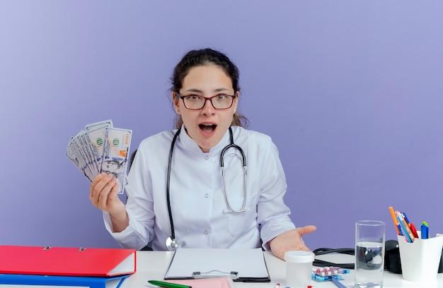 Giovane medico femminile impressionato che porta veste medica e stetoscopio che si siede allo scrittorio con gli strumenti medici che tengono soldi che sembrano isolati