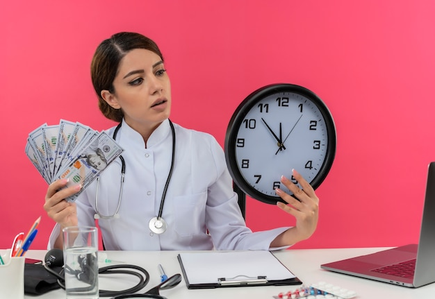 Impressed young female doctor wearing medical robe and stethoscope sitting at desk with medical tools and laptop holding money and clock looking at clock