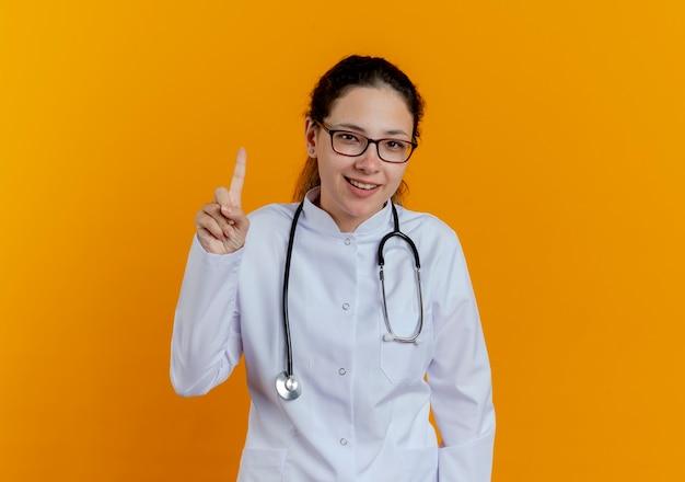 Impressionato giovane medico femminile che indossa abito medico e stetoscopio con i punti di occhiali in alto isolato